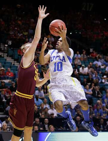 FILE - This March 14, 2013 file photo shows UCLA's Larry Drew II (10) as he goes up for a shot against Arizona State's Jonathan Gilling during the first half of a Pac-12 men's tournament NCAA college basketball game in Las Vegas. The neon-colored jerseys and camouflage-covered shorts debuted by six teams in their post-season conference championships ahead of the NCAA men's basketball tournament weren't well received in the press and social media. The changes happened to be in line with fashion runways and in recreational athleticwear, where highlighter brights and creative camo have been bona fide trends, and alternate uniforms have become part of the college football and basketball landscape, but on the court, these uniforms still made fans cringe. (AP Photo/Julie Jacobson, file) Photo: Julie Jacobson