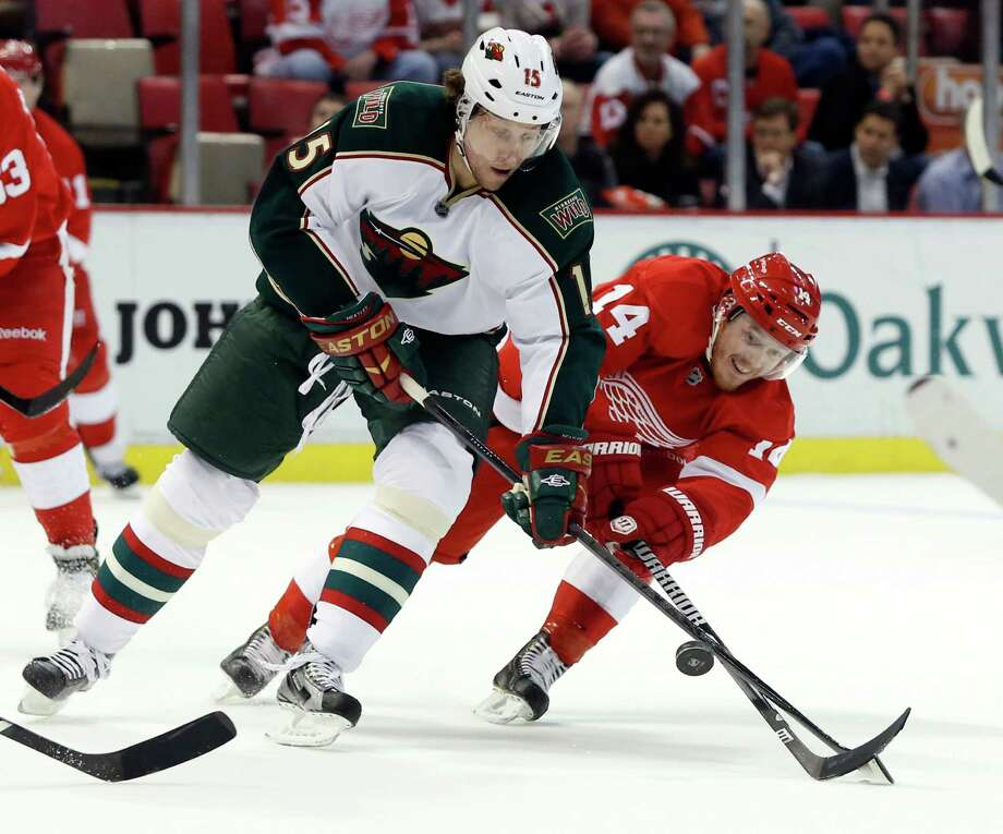 The Red Wings' Gustav Nyquist, right, and the Wild's Dany Heatley try to corral the bouncing puck. Photo: Duane Burleson, FRE / FR38952 AP