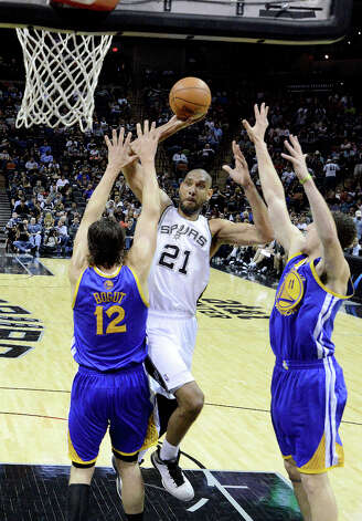 The Spurs' Tim Duncan shoots over Andrew Bogut (12) and Klay Thompson (11) of Golden State during second-half NBA action at the AT&T Center on Wednesday, March 20, 2013. The Spurs won, 104-93. Photo: Billy Calzada, San Antonio Express-News / San Antonio Express-News
