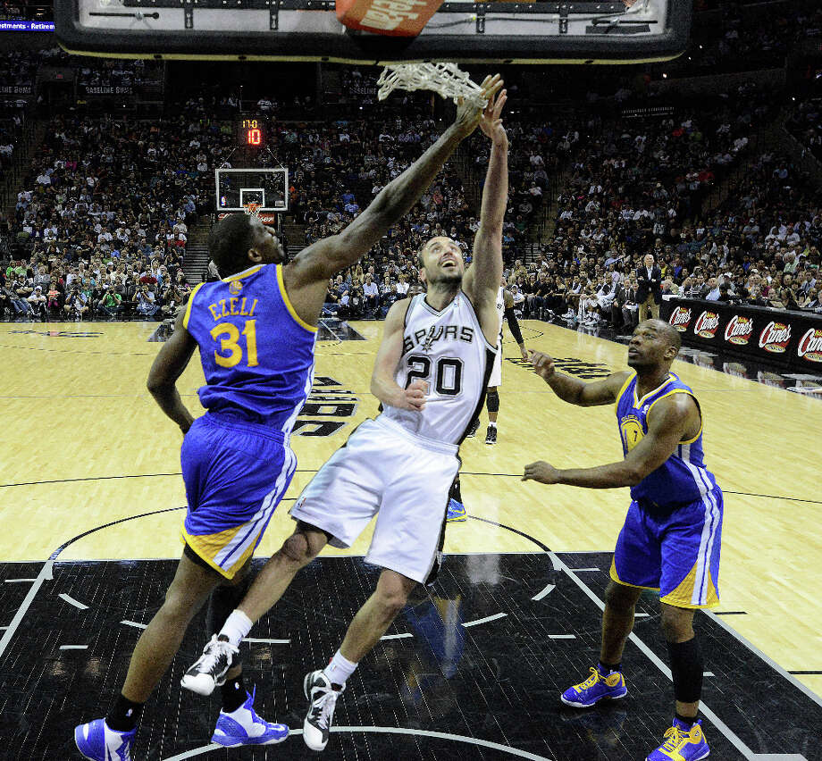 Manu Ginobili (20) of the Spurs shoots a layup as Festus Ezeli of Golden State attempts to block the shot during second-half NBA action at the AT&T Center on Wednesday, March 20, 2013. The Spurs won, 104-93. Photo: Billy Calzada, San Antonio Express-News / San Antonio Express-News