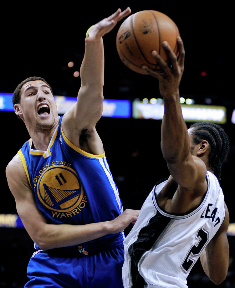 Golden State Warriors' Klay Thompson, left, attempts a steal from San Antonio Spurs' Kawhi Leonard during the first half of an NBA basketball game, Wednesday, March 20, 2013, in San Antonio. Photo: Darren Abate, Associated Press / FR115 AP