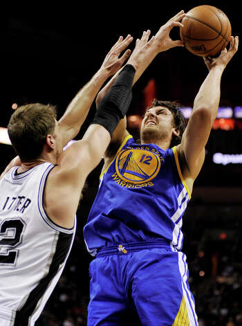Golden State Warriors' Andrew Bogut (12) shoots over San Antonio Spurs' Tiago Splitter, of Brazil, during the second half of an NBA basketball game, Wednesday, March 20, 2013, in San Antonio. San Antonio won 104-93. Photo: Darren Abate, Associated Press / FR115 AP