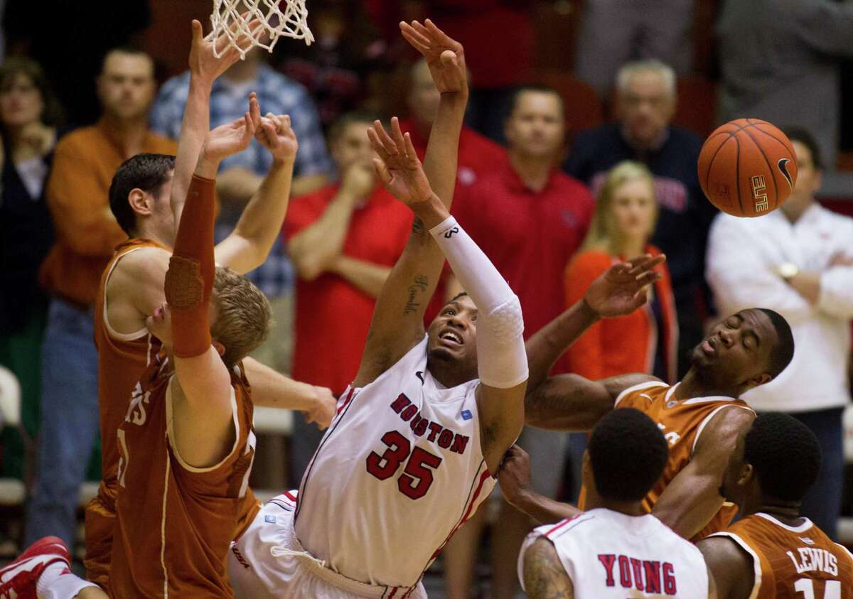 U of H forward TaShawn Thomas (35) is swarmed by Texas players while taking a shot during the second half of the CBI men's postseason basketball tournament at Hofheinz Pavillion on Wednesday, March 20, 2013, in Houston.