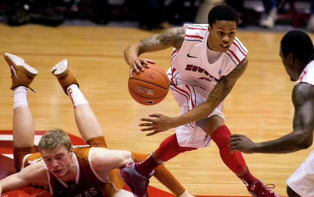 U of H guard Joseph Young (0) dribbles past Texas forward Connor Lammert (21) during the second half of the CBI men's postseason basketball tournament at Hofheinz Pavillion on Wednesday, March 20, 2013, in Houston. Photo: J. Patric Schneider, For The Chronicle / © 2013 Houston Chronicle