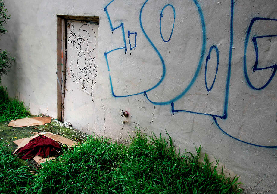 On Haight Street, a person left behind a blanket near an old door into the school. The former UC Extension site at Haight and Laguna Streets in San Francisco, Calif. is full of litter, graffiti and a hangout for the homeless Wednesday March 20, 2013. Photo: Brant Ward, The Chronicle / ONLINE_YES