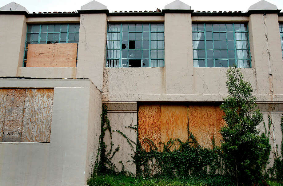 The old school shows evidence of vandalism, broken windows only partially covered with plywood. The former UC Extension site at Haight and Laguna Streets in San Francisco, Calif. is full of litter, graffiti and a hangout for the homeless Wednesday March 20, 2013. Photo: Brant Ward, The Chronicle / ONLINE_YES