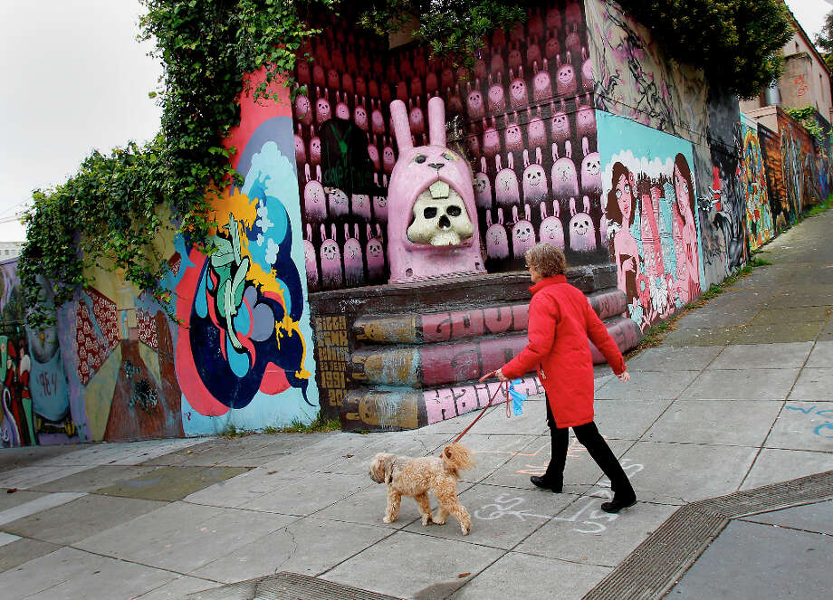 A woman walks her dog past the colorful corner of Haight and Laguna Streets, site of the old school. The former UC Extension site at Haight and Laguna Streets in San Francisco, Calif. is full of litter, graffiti and a hangout for the homeless Wednesday March 20, 2013. Photo: Brant Ward, The Chronicle / ONLINE_YES