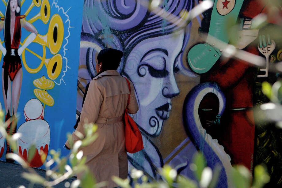 A woman walks passed the murals on Haight Street on March 17th, 2013 in San Francisco, Calif. The former UC Extension site at Haight and Laguna has been abandoned for some time now. While neighborhood associations have tried their hardest to make it look pleasing with there are bright, vibrant murals on one side, much of it looks like it's just an old building. The grass is overgrown with constant broken glass around it. The city's planning department approved a plan to turn it into housing, with construction slated to begin in summer 2013. Photo: Jessica Olthof, The Chronicle / ONLINE_YES