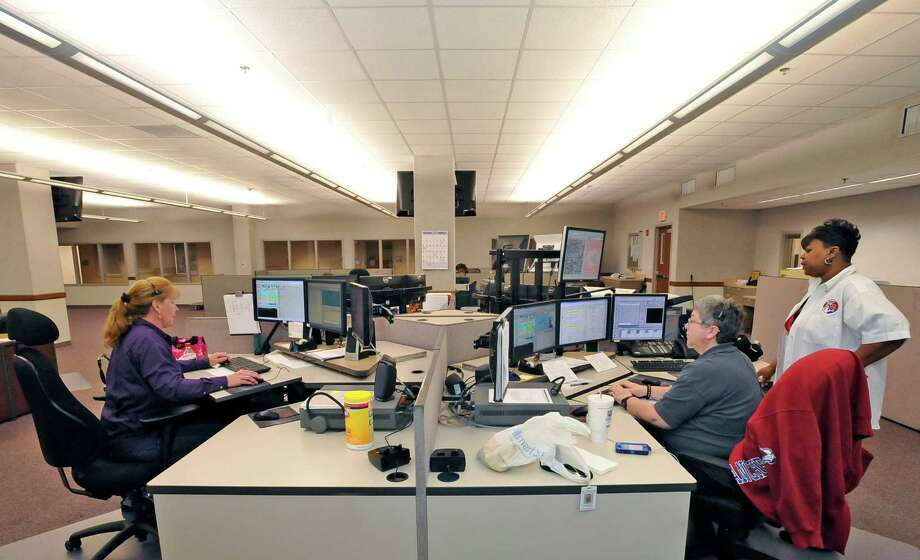 At the 911 Operations Center at the corner of Orleans and Forsythe, Carolyn Lewis, right, a 20 year veteran, is the Training/QA Supervisior/Dispatch Operator.  Here she talking with telecommunicators Lynne Wisby, left, and Robin Ogden, right.  Dave Ryan/The Enterprise Photo: Dave Ryan