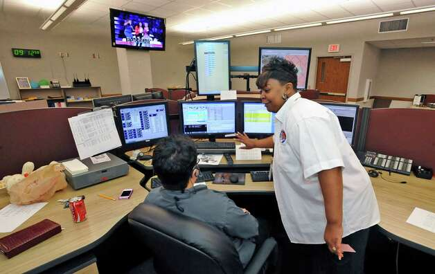 "At the 911 Operations Center at the corner of Orleans and Forsythe, Carolyn Lewis, right, a 20 year veteran, is the Training/QA Supervisior/Dispatch Operator.  Here she, is talking to telecommunicator Robin Ogden, left, who was working her station.  about how the system works on ""the floor.""  Dave Ryan/The Enterprise Photo: Dave Ryan"
