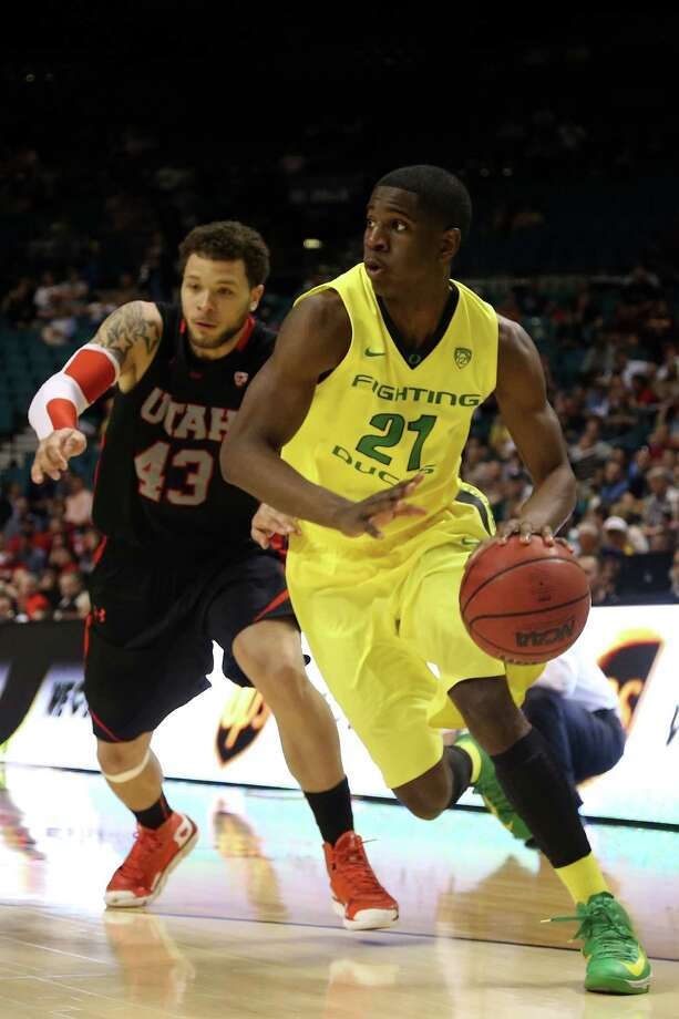 LAS VEGAS, NV - MARCH 15:  Damyean Dotson #21 of the Oregon Ducks drives on Cedric Martin #43 of the Utah Utes in the second half during the semifinals of the Pac-12 tournament at the MGM Grand Garden Arena on March 14, 2013 in Las Vegas, Nevada. Photo: Jeff Gross, Getty Images / 2013 Getty Images