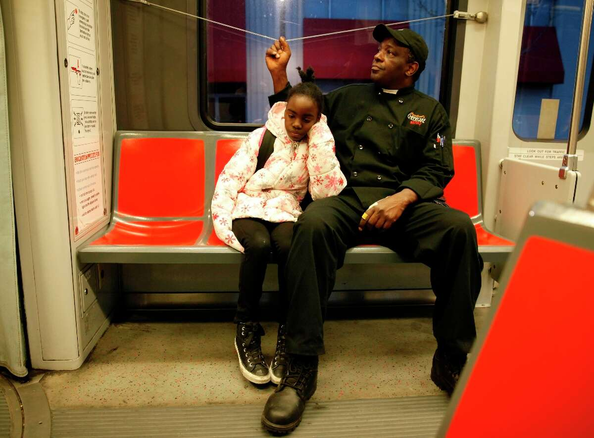 Thomas Bailey (right) signals to get off at the next stop as he rides on the T Muni light rail with his daughter, Ashanti Bailey (left), 10, to school on Wednesday, March 20, 2013 in San Francisco, Calif.