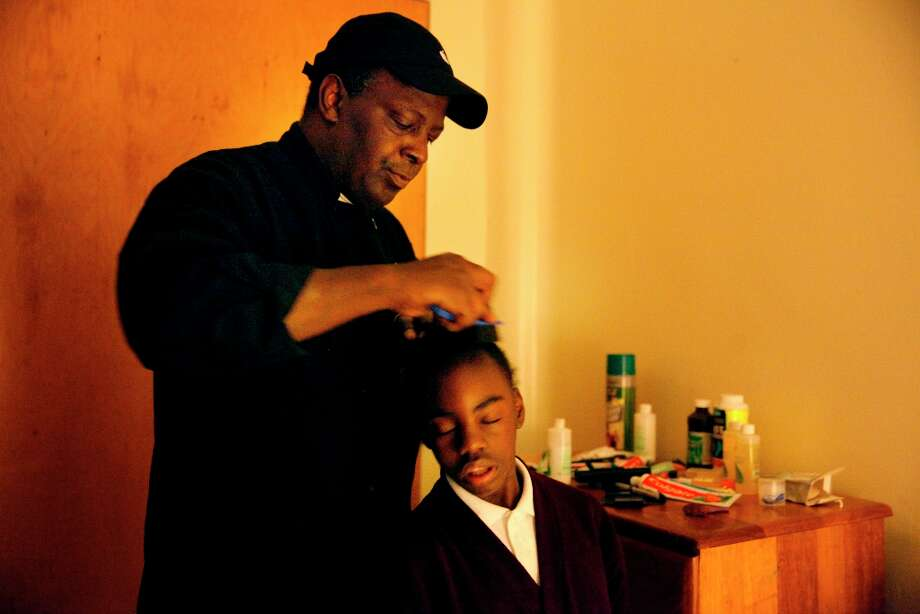 Thomas Bailey (l to r) brushes his daughter Ashanti Bailey's, 10, hair as they prepare to leave for her school in their new room at Raphael House on Wednesday, March 20, 2013 in San Francisco, Calif. Photo: Lea Suzuki, The Chronicle / ONLINE_YES