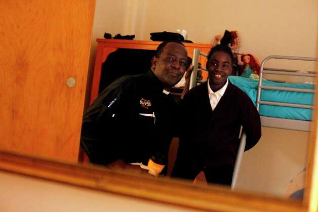 Thomas Bailey (l to r) and his daughter Ashanti Bailey 10, are seen reflected in a mirror in their new room at Raphael House on Monday, March 18, 2013 in San Francisco, Calif. Photo: Lea Suzuki, The Chronicle / ONLINE_YES