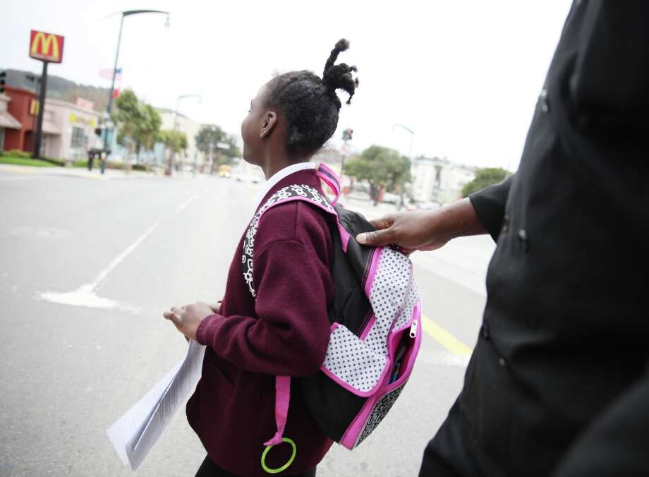 Thomas Bailey (right) keeps a hold of his daughter Ashanti Bailey's, 10, backpack as they cross Third Street after school on Monday, March 18, 2013 in San Francisco, Calif. Photo: Lea Suzuki, The Chronicle / ONLINE_YES