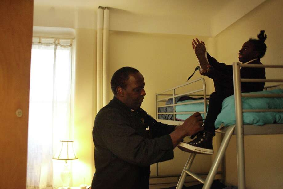 Thomas Bailey helps remove his daughter Ashanti Bishop's, 10, shoes as they arrive at their new room after their intake appointment at Raphael House on Monday, March 18, 2013 in San Francisco, Calif. Photo: Lea Suzuki, The Chronicle / ONLINE_YES