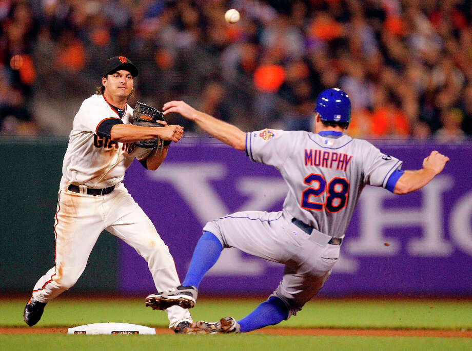 San Francisco Giants' second baseman Ryan Theriot (5) turns the double play while avoiding New York Mets' Daniel Murphy (28) during the seventh inning of a baseball game in San Francisco, Monday, July 30, 2012. New York Mets' Ruben Tejada was out at first base. Photo: Tony Avelar, Associated Press / FR155217 AP