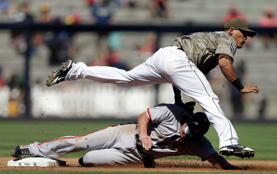 San Diego Padres shortstop Everth Cabrera jumps over San Francisco Giants' Ryan Theriot after getting the out when Theriot tried to steal second base during the second inning in a baseball game in San Diego, Sunday, Sept. 30, 2012. Photo: Gregory Bull, Associated Press / AP