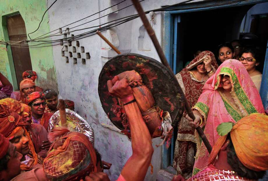 An Indian woman from the village of Barsana hits villagers from Nandgaon with a wooden stick during the Lathmar Holy festival the legendary hometown of Radha, consort of Hindu God Krishna, in Barsana, 115 kilometers (71 miles) from New Delhi, India, Thursday, March 21, 2013. During Lathmar Holi the women of Barsana beat the men from Nandgaon, the hometown of Krishna, with wooden sticks in response to their teasing as they depart the town. (AP Photo/Manish Swarup) Photo: Manish Swarup, Associated Press / AP