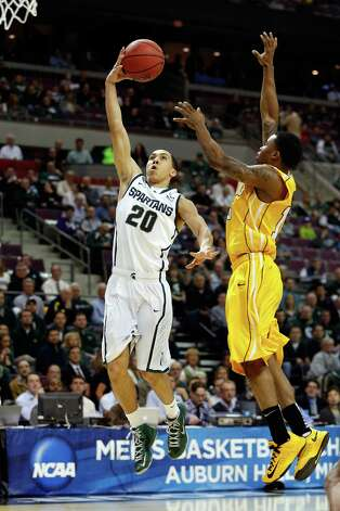 AUBURN HILLS, MI - MARCH 21:  Travis Trice #20 of the Michigan State Spartans drives for a shot attempt in the first half against Erik Buggs #15 of the Valparaiso Crusaders during the second round of the 2013 NCAA Men's Basketball Tournament at at The Palace of Auburn Hills on March 21, 2013 in Auburn Hills, Michigan. Photo: Gregory Shamus, Getty Images / 2013 Getty Images