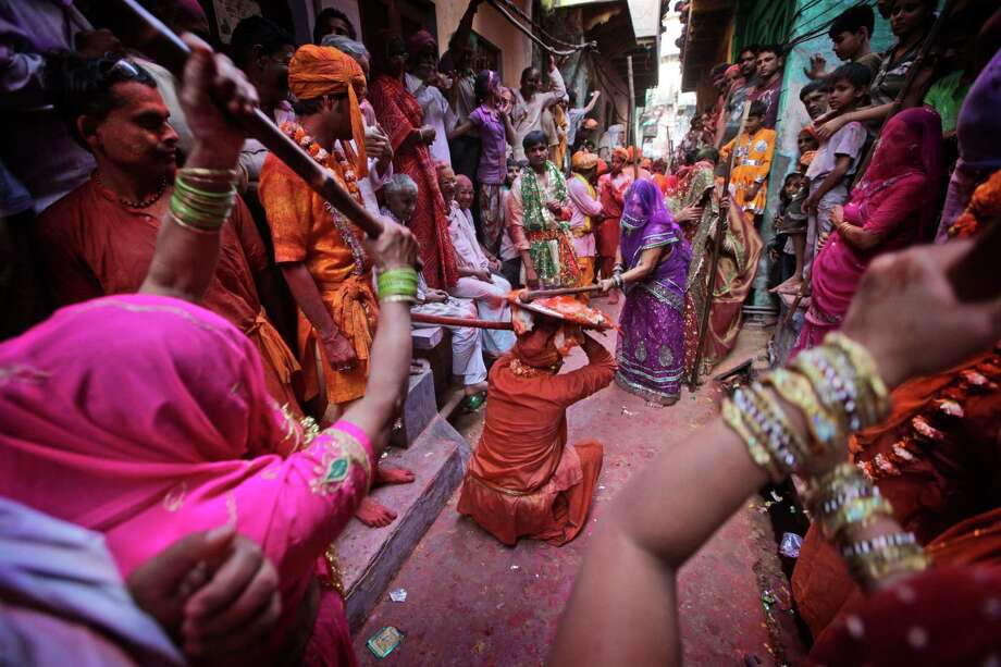 Indian women from Barsana village hit villagers from Nandgaon with a wooden stick during the Lathmar Holy festival the legendary hometown of Radha, consort of Hindu God Krishna, in Barsana, 115 kilometers (71 miles) from New Delhi, India, Thursday, March 21, 2013. During Lathmar Holi the women of Barsana beat the men from Nandgaon, the hometown of Krishna, with wooden sticks in response to their teasing as they depart the town. (AP Photo/Manish Swarup) Photo: Manish Swarup, Associated Press / AP