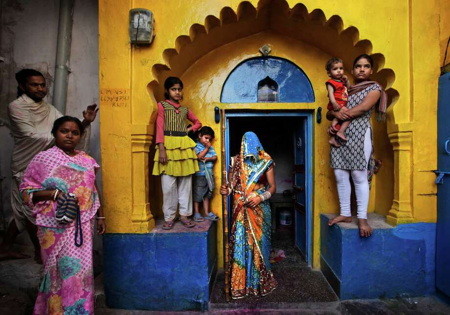 A newly wed Indian woman from Barsana village waits with a wooden stick at the door step of her house, for the arrival of villagers from Nandgaon during the Lathmar Holy festival the legendary hometown of Radha, consort of Hindu God Krishna, in Barsana, 115 kilometers (71 miles)  from New Delhi, India , Thursday, March 21, 2013. During Lathmar Holi the women of Barsana beat the men from Nandgaon, the hometown of Krishna, with wooden sticks in response to their teasing as they depart the town. (AP Photo/Manish Swarup) Photo: Manish Swarup, Associated Press / AP