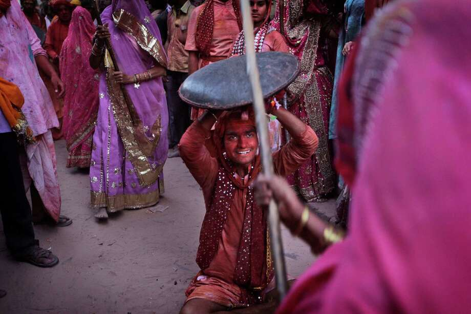 An Indian woman from Barsana village hits a villager from Nandgaon with a wooden stick during the Lathmar Holy festival the legendary hometown of Radha, consort of Hindu God Krishna, in Barsana, 115 kilometers (71 miles) from New Delhi, India, Thursday, March 21, 2013. During Lathmar Holi the women of Barsana beat the men from Nandgaon, the hometown of Krishna, with wooden sticks in response to their teasing as they depart the town. (AP Photo/Manish Swarup) Photo: Manish Swarup, Associated Press / AP