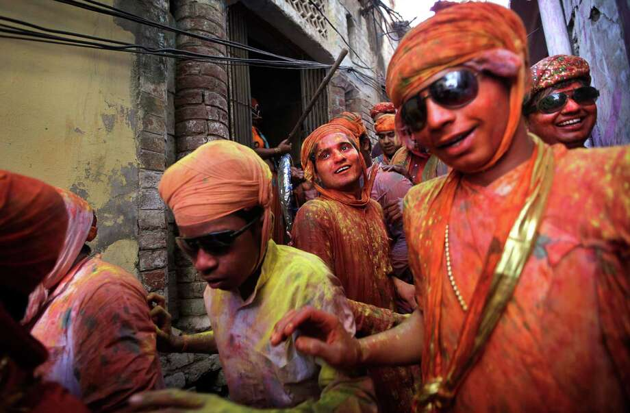 Indian villagers from Nandgaon arrive in Barsana village during the Lathmar Holy festival, the legendary hometown of Radha, consort of Hindu God Krishna, in Barsana, 115 kilometers (71 miles) from New Delhi, India, Thursday, March 21, 2013. During Lathmar Holi the women  of Barsana beat the men from Nandgaon, the hometown of Krishna, with wooden sticks in response to their teasing as they depart the town. (AP Photo/Manish Swarup) Photo: Manish Swarup, Associated Press / AP