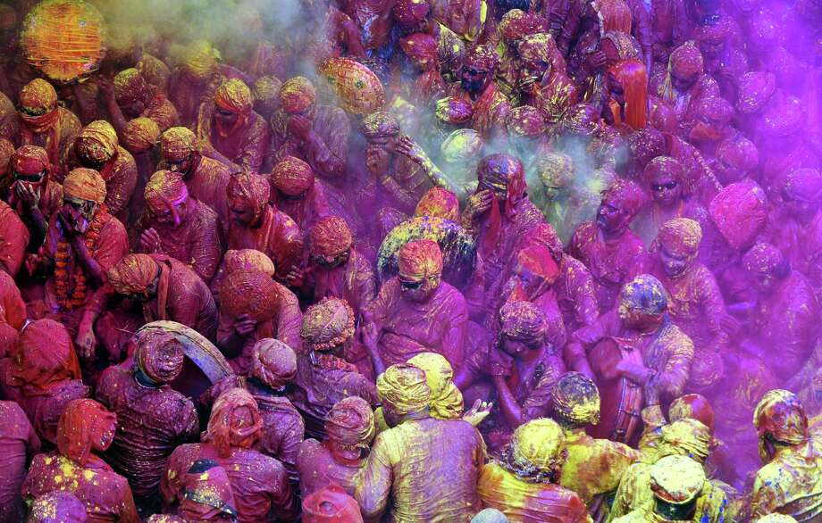 Indian Hindu devotees throw colored powder at the Radha Rani temple during the Lathmar Holi festival in Barsana on March 21, 2013. Lathmar Holi is a local celebration, but it takes place well before the national Holi day on March 27. AFP PHOTO/ Sanjay KanojiaSanjay Kanojia/AFP/Getty Images Photo: SANJAY KANOJIA, AFP/Getty Images / AFP
