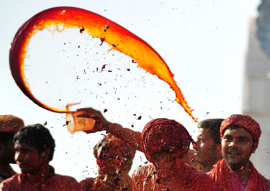 Indian Hindu devotees throw colored water at the Radha Rani temple during the Lathmar Holi festival in Barsana on March 21, 2013. Lathmar Holi is a local celebration, but it takes place well before the national Holi day on March 27. AFP PHOTO/ Sanjay KanojiaSanjay Kanojia/AFP/Getty Images Photo: SANJAY KANOJIA, AFP/Getty Images / AFP