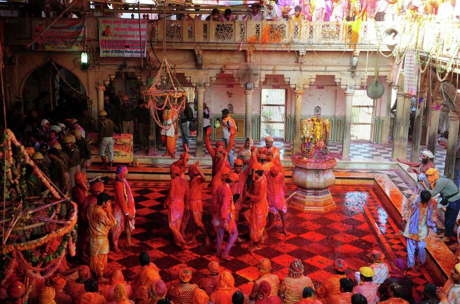 Indian Hindu devotees dance covered in colored powder at the Radha Rani temple during the Lathmar Holi festival in Barsana on March 21, 2013. Lathmar Holi is a local celebration, but it takes place well before the national Holi day on March 27. AFP PHOTO/ Sanjay KanojiaSanjay Kanojia/AFP/Getty Images Photo: SANJAY KANOJIA, AFP/Getty Images / AFP