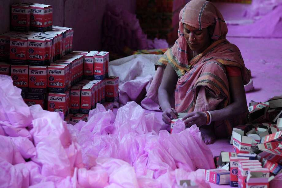 "An Indian labourer packs colored powder, known as ""gulal"", to be used during the forthcoming spring festival of Holi, on the outskirts of Siliguri on March 20, 2013. Holi, the popular Hindu spring festival colours observed in India at the end of the winter season on the last full moon of the lunar month, will be celebrated March 27 this year. AFP PHOTO/Diptendu DUTTADIPTENDU DUTTA/AFP/Getty Images Photo: DIPTENDU DUTTA, AFP/Getty Images / AFP"