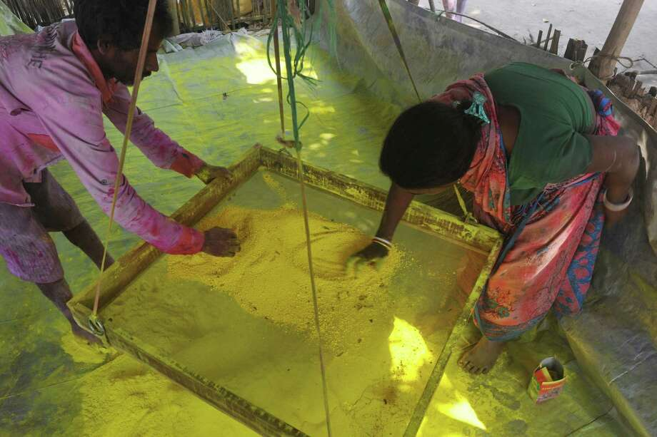 "Indian labourers sift colored powder, known as ""gulal"", to be used during the forthcoming spring festival of Holi, on the outskirts of Siliguri on March 20, 2013. Holi, the popular Hindu spring festival colours observed in India at the end of the winter season on the last full moon of the lunar month, will be celebrated March 27 this year. AFP PHOTO/Diptendu DUTTADIPTENDU DUTTA/AFP/Getty Images Photo: DIPTENDU DUTTA, AFP/Getty Images / AFP"