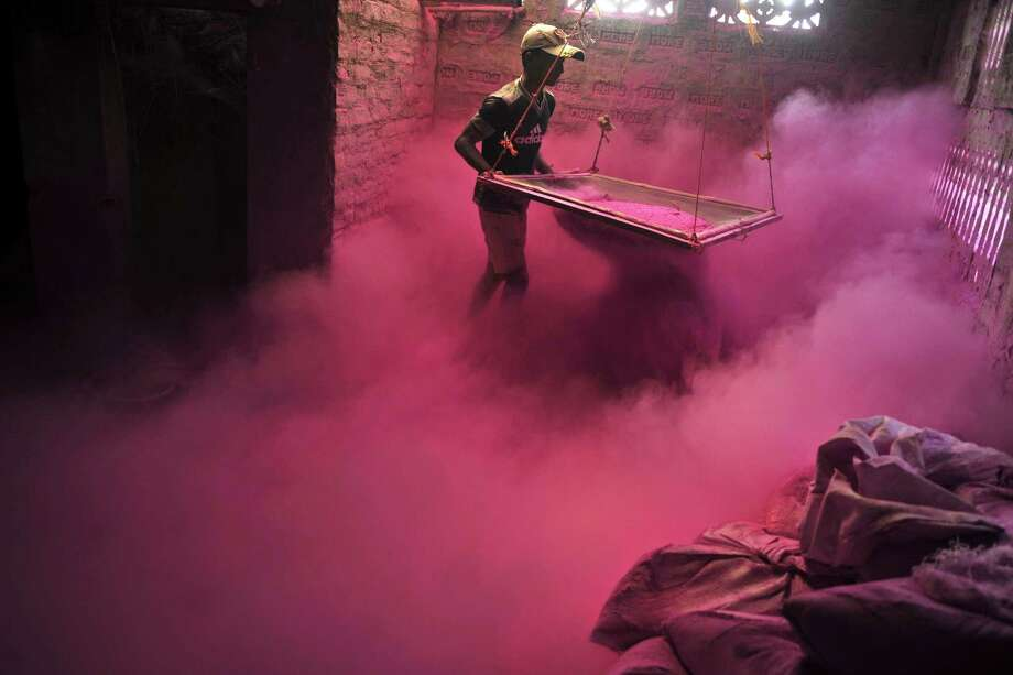 "An Indian labourer sifts colored powder, known as ""gulal"", to be  used during the forthcoming spring festival of Holi, on the outskirts of Siliguri on March 20, 2013. Holi, the popular Hindu spring festival colours observed in India at the end of the winter season on the last full moon of the lunar month, will be celebrated March 27 this year. AFP PHOTO/Diptendu DUTTADIPTENDU DUTTA/AFP/Getty Images Photo: DIPTENDU DUTTA, AFP/Getty Images / AFP"