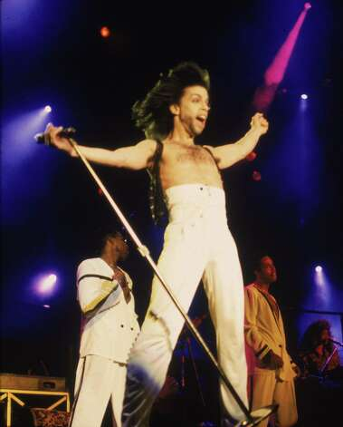 Prince stands on stage with his arms outstretched, wearing high-waisted white pants, circa 1990. Photo: Frank Micelotta, Getty Images / 2003 Getty Images