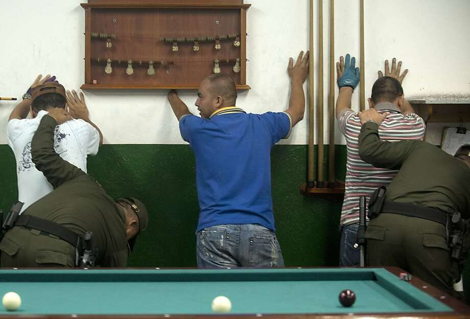 Behind the eight ball:Colombian soldiers frisk pool players at Commune 13, a shantytown with a high rate of violence in Medellin. Photo: Raul Arboleda, AFP/Getty Images
