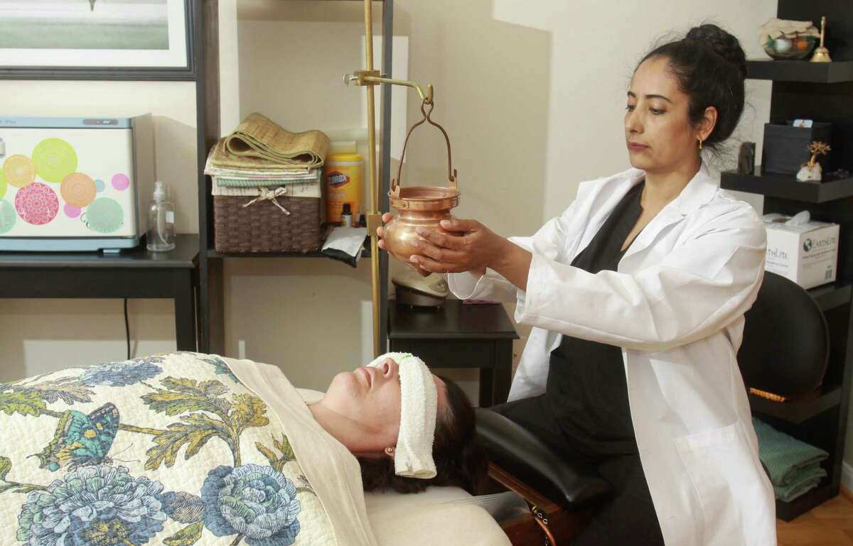 Sharon Kapp gives a shirodhara treatment, which is part of a panchakarma detox, to Rose Silva at the Healing Tree: Houston Yoga & Ayurveda Wellness Center.