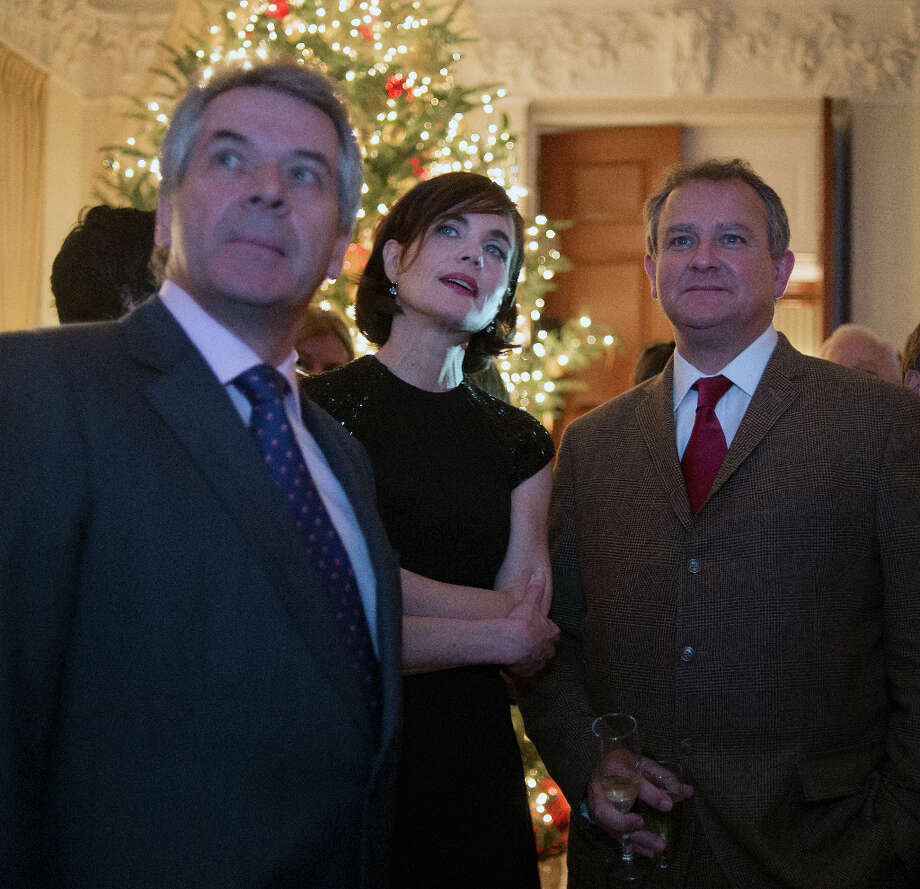 British Ambassador the the U.S. Sir Peter Westmacott, left, actress Elizabeth McGovern, center, and actor Hugh Bonneville watch a brief preview of the upcoming 3rd season of Downton Abbey. The actors attended a reception in their honor for  at the British Ambassador's Residence in Washington DC, December 14, 2012 .(Photo by John McDonnell/The Washington Post via Getty Images) Photo: The Washington Post, The Washington Post/Getty Images / 2012 The Washington Post