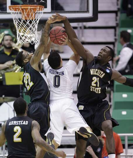 Wichita State's Carl Hall (22) and teammate Ehimen Orukpe (21) block the shot of Pittsburgh's James