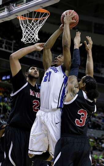 Saint Louis forward Dwayne Evans (21) shoots in between New Mexico State center Sim Bhullar (2) and