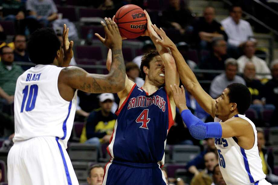 Matthew Dellavedova #4 of the St. Mary's Gaels looks to pass in the first half against the Tarik Black #10 and Geron Johnson #55 of the Memphis Tigers. Photo: Gregory Shamus, Getty Images / 2013 Getty Images