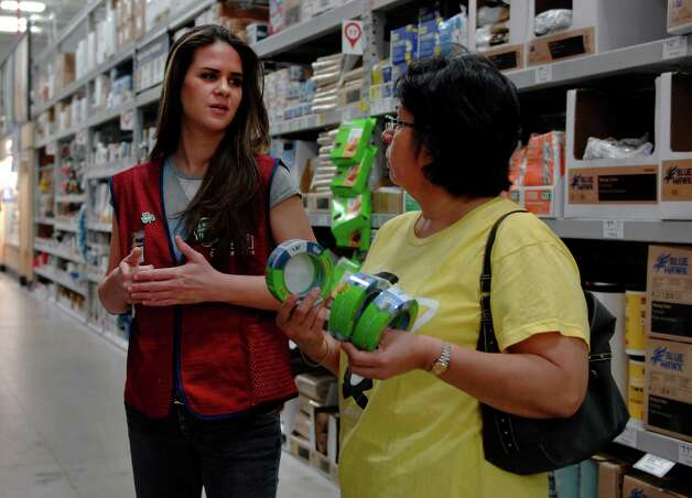 Heather Nunley (left) a temporary Lowe's associate assists Noemi Graham of San Antonio with her painting needs at the Austin Highway Lowe's March 16, 2013. Lowe's has hired about 300 temporary workers to help accommodate homeowners shopping this weekend for Do-it-Yourself projects supplies. Photo: Steve Faulisi, San Antonio Express-News / ©2013 San Antonio Express-News