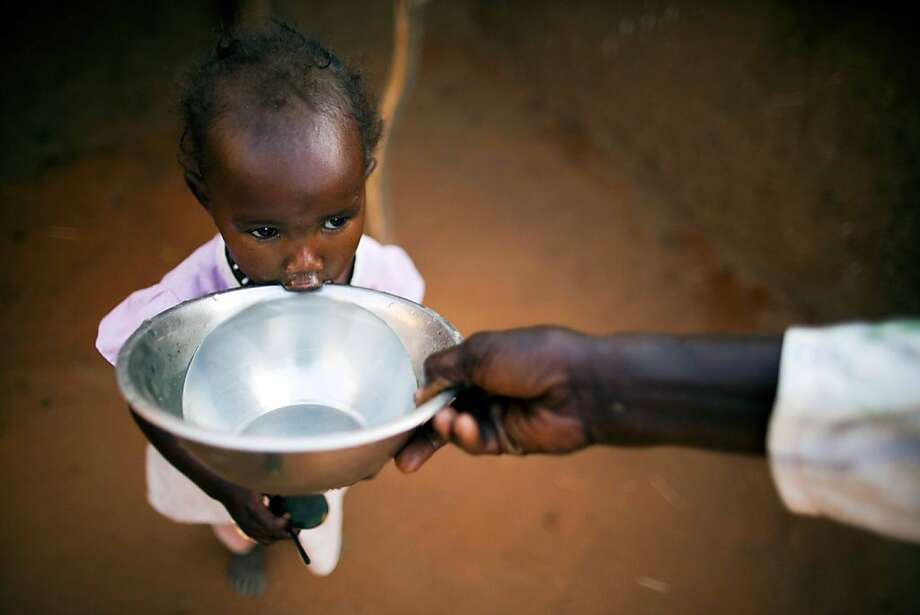 A precious drink:A mother offers water to her child at the Abu Shouk camp for internally displaced persons in El-Fasher, Sudan. Water at the camp is scarce, forcing refugees to walk miles to collect it and haul it back. Photo: Albert Gonzalez Farran, AFP/Getty Images