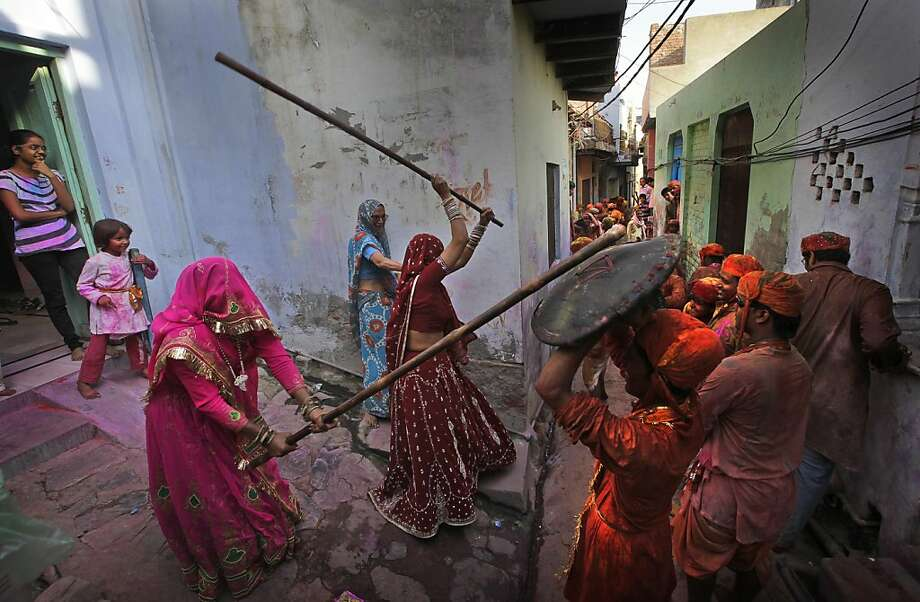 "They have thin skins, short tempers and big sticks: Indian woman from the village of Barsana ""beat"" men from the village from Nandgaon with wooden poles during the Lathmar Holi festival. The women traditionally club the men to get them to stop teasing them. Nandgaon is the legendary hometown of Krishna; his consort, Radha, was supposedly raised in Barsana. Photo: Manish Swarup, Associated Press"