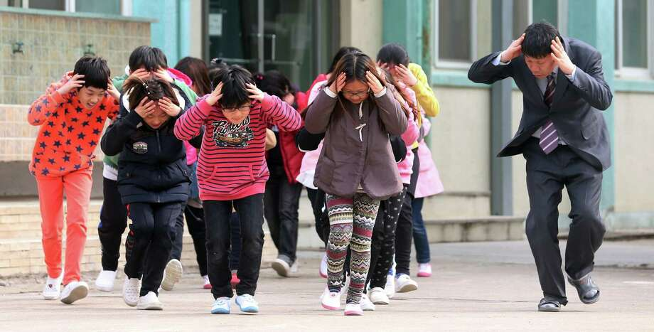 Duck and cover, circa 2013: The Cold War is alive in South Korea. South Korean students and a teacher rush to a shelter during a civil defense drill. Photo: Bae Jung-hyun, Associated Press
