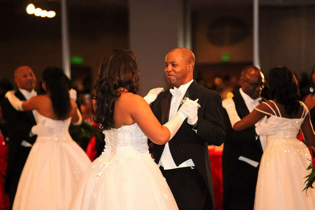 Debutantes dance with their fathers at the Pals Social Club's 2012 ball. Debutantes must learn two dances for the ball and do a full-court bow. Photo: Red Baklava Photography