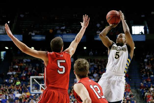 Junior Cadougan #5 of the Marquette Golden Eagles shoots against JP Kuhlman #5 and Nik Cochran #12 of the Davidson Wildcats in the first half. Photo: Kevin C. Cox, Getty Images / 2013 Getty Images