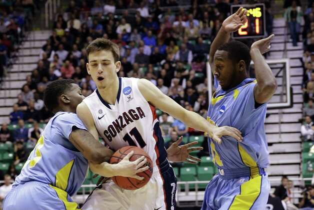 Gonzaga's David Stockton (11) is fouled by Southern University's YonDarius Johnson, left, while Christopher Hyder, right,  watches in the first half during a second-round game in the NCAA college basketball tournament in Salt Lake City, Thursday, March 21, 2013. (AP Photo/Rick Bowmer) Photo: Rick Bowmer, Associated Press / AP