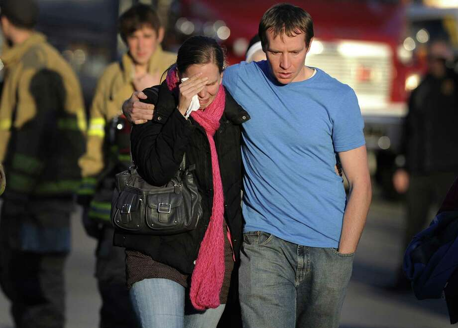 Alissa Parker, left, and her husband, Robbie Parker,  leave the firehouse staging after receiving word that their six-year-old daughter Emilie was one of the 20 children killed in the Sandy Hook School shooting in Newtown, Conn. Photo: Jessica Hill, FRE / FR125654 AP
