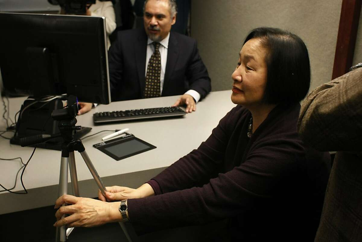 Oakland Mayor Jean Quan adjusts the camera to take her photo for the Oakland municipal identification card on Friday, Feb.1. The municipal identification doubles as a debit card and is aimed at undocumented immigrants as well as people who wish to not have their gender on the card.
